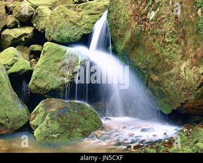 Weir in mountain stream. Colorful leaves  on stones into water. Mossy boulders. - Stock Photo
