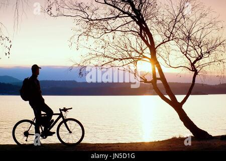 Young man cyclist silhouette on blue sky and sunset background on the beach. End of season at lake. - Stock Photo