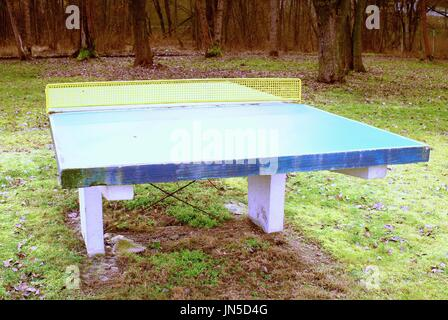 Concrete Ping Pong Table; Outdoors Green Concrete Ping Pong Table, Rusty  Yellow Net   Stock Photo