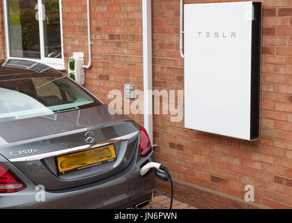 A Mercedes C class Hybrid electric car being charged ( via a Rolec charger) from solar PV stored in a Tesla Powerwall - Stock Photo