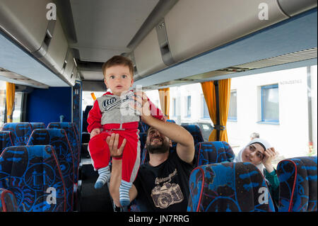 Passau, Germany - August 1, 2015: Family from Syria in the bus on the way from registration center in Passau, southern - Stock Photo