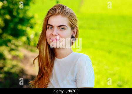 Portrait of a young beautiful woman with wooden tunnels in her ears. - Stock Photo