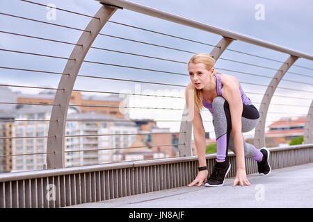 A young woman prepares to break into a sprint on the Millennium Footbridge - Stock Photo
