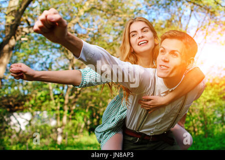 Portrait of happy couple raising their hands in open air. - Stock Photo