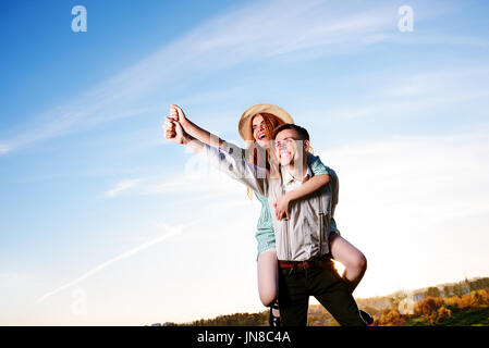 Young man piggybacking his happy girlfriend with raised hand. Cheerful lovers dreaming. - Stock Photo