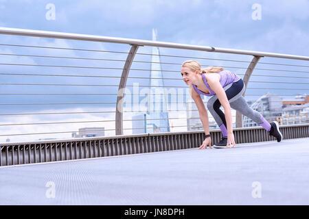 A young woman prepares to sprint on the Millennium Footbridge - Stock Photo