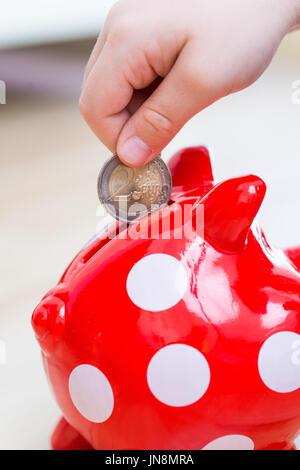 child thrown into Piggy coin - two euro - Stock Photo