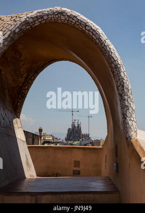 the unfinished Sagrada Familia cathedral designed by Gaudi seen through an archway on the roof of Casa Mila, or - Stock Photo
