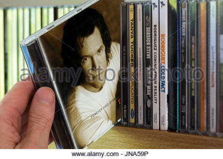 Forever and Ever, Randy Travis CD being chosen from a shelf of other CD's, Dorset, England - Stock Photo