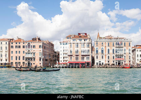 Venice, Veneto, Italy. Gondoliers rowing their gondolas on the Grand Canal past the Hotel Bauer Palazzo and  the - Stock Photo