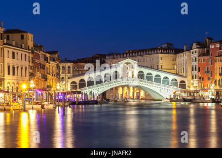 Venice,  Veneto, Italy view of the Rialto Bridge during blue hour with reflections on the water and illuminated - Stock Photo