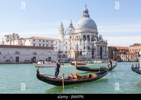 March 2017 Grand Canal, Venice, Italy. Two gondoliers rowing their gondolas past the Basilica Santa Maria della - Stock Photo