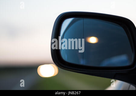 Car lights reflecting in the side mirror of a car parked on the curb of a highway - Stock Photo