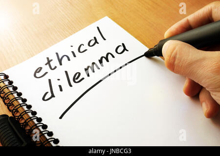 Ethical dilemma written in a note. - Stock Photo
