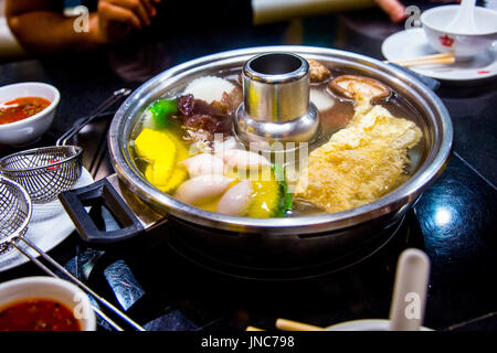 Thai hotpot (Tom Yum soup) at a restaurant, food cooked at the table - Stock Photo