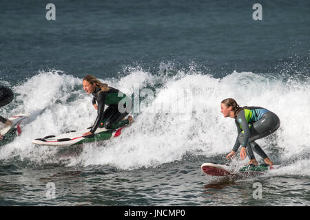 Two young australian woman riding a wave on their surfboard in Sydney,Australia - Stock Photo