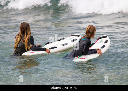 Two Australian girls in the ocean off a Sydney beach wearing wetsuits and holding onto their surfboards,Australia - Stock Photo