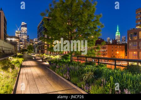 High Line promenade at twilight with city lights and illuminated skyscrapers. Chelsea, Manhattan, New York City - Stock Photo