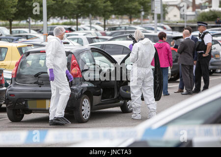 A man has been arrested after allegedly slitting a woman's throat in a busy shopping centre car park this morning - Stock Photo