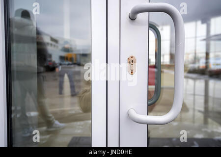 Close-up of glass office doors with keyhole - Stock Photo