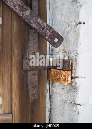 The metal handle of a wooden shutter on a white wall of a house - Stock Photo