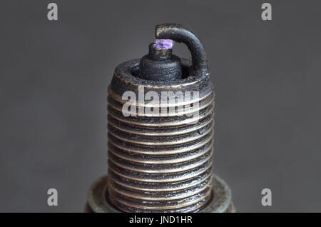 Broken dirty spark plug with blue sparkle - Stock Photo