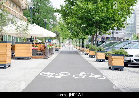 City street with long bicycle lane near outdoor cafe - Stock Photo