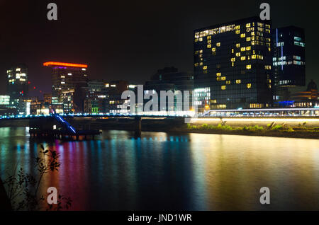 Night cityscape of bay in Dusseldorf with reflection at Rhine river; Urban night scene with hotel, restaurants and - Stock Photo