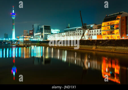 Night scene of Rhein river at night in Dusseldorf. View from Media harbor on Rheinturm tower, cafe on water and - Stock Photo