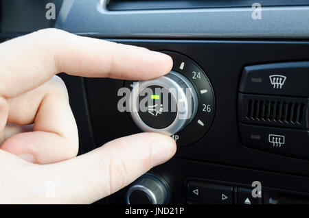 Mens hand setting up the temperature on car climate control system - Stock Photo