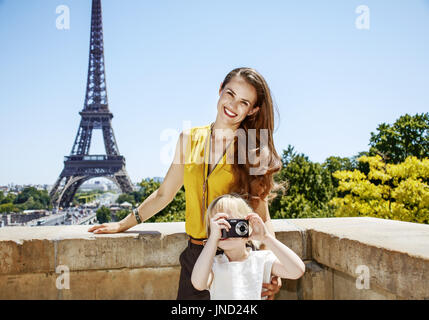 Having fun time near the world famous landmark in Paris. happy mother and daughter taking photo with digital camera - Stock Photo