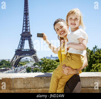 Having fun time near the world famous landmark in Paris. Portrait of happy mother and daughter taking photo with - Stock Photo