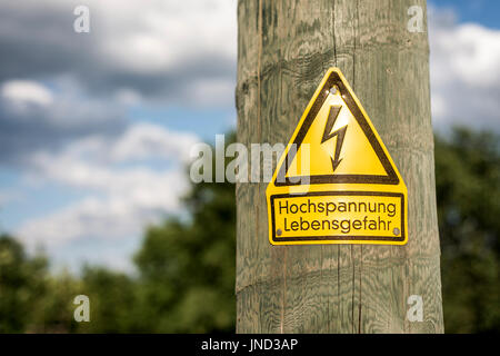 German high voltage sign mounted on wooden pole with green tree in the background - Stock Photo