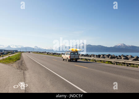 Car with Kayak on the roof drives along Homer Spit, Homer, Alaska, USA - Stock Photo