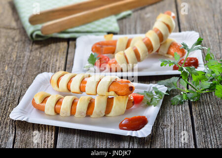 Baked Vienna sausages wrapped with puff pastry fresh from the oven, often served as a children's meal - Stock Photo
