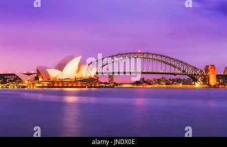 Sydney, Australia - 11 July 2015: Sydney opera house and Harbour bridge at sunset against colourful magenta sky - Stock Photo