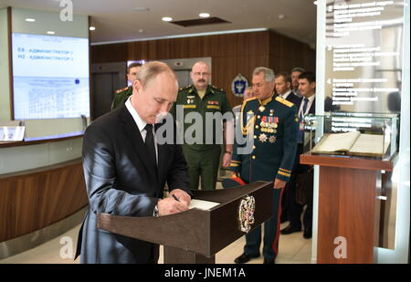 St Petersburg, Russia. 30th July, 2017. Russia's president Vladimir Putin (front) signs the distinguished visitors' - Stock Photo