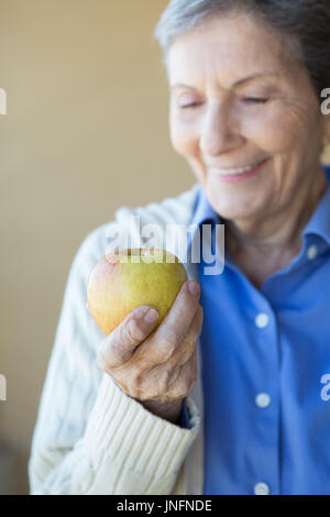 Elderly woman eating an apple. - Stock Photo
