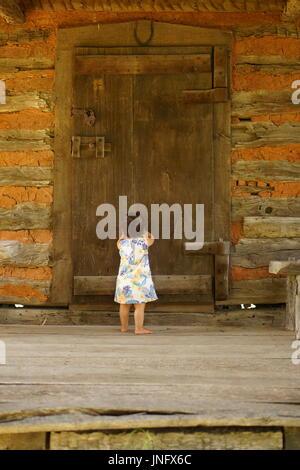 Baby Girl knocking on a big door - Stock Photo