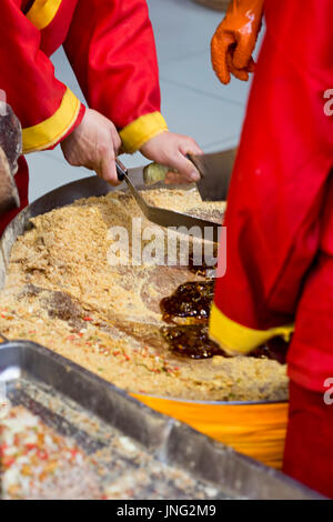 Group of Chinese workers making and selling caramel sweets, Beijing market, China - Stock Photo