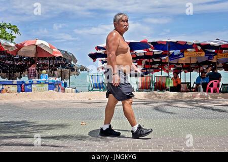Senior exercise. Asian shirtless man walking along the street as a keep fit exercise. Thailand Southeast Asia - Stock Photo
