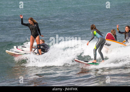 Teenage girls close up young women surfing on surfboards at Avalon beach in Sydney,Australia - Stock Photo