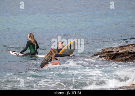 Teenage girls young women surfing on surfboards at Avalon beach in Sydney,Australia - Stock Photo