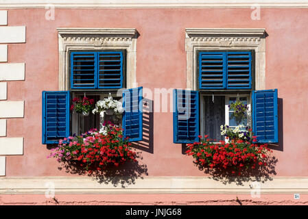 Blue windows with flowerpots of a house on Piata Mica (Lesser Square), Upper Town of Sibiu, Romania - Stock Photo