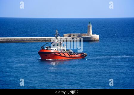 Tug boat in the Grand Harbour with the lighthouse to the rear, Valletta, Malta, Europe. - Stock Photo