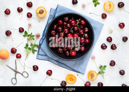 Berry flat lay with sweet cherries, apricots and clover leaf on white background, top view - Stock Photo
