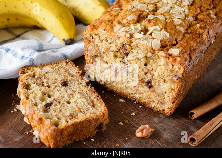 Protein banana bread loaf with walnuts and cinnamon on wooden board. Closeup view - Stock Photo