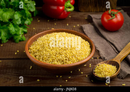 Bulgur Gluten Free Wheat Grains in bowl on wooden table - Stock Photo