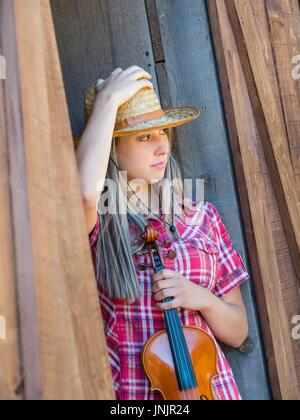 Country-girl and violin standing on door holding hat looking away nostalgia nostalgic alpfabet model-release released - Stock Photo