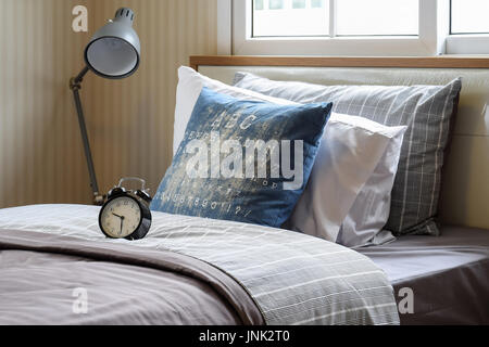 black alarm clock in cozy bedroom interior with pillows and reading lamp - Stock Photo